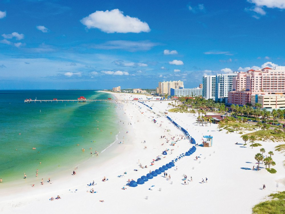 Aerial view of lively Clearwater Beach with white sands and emerald-green waters