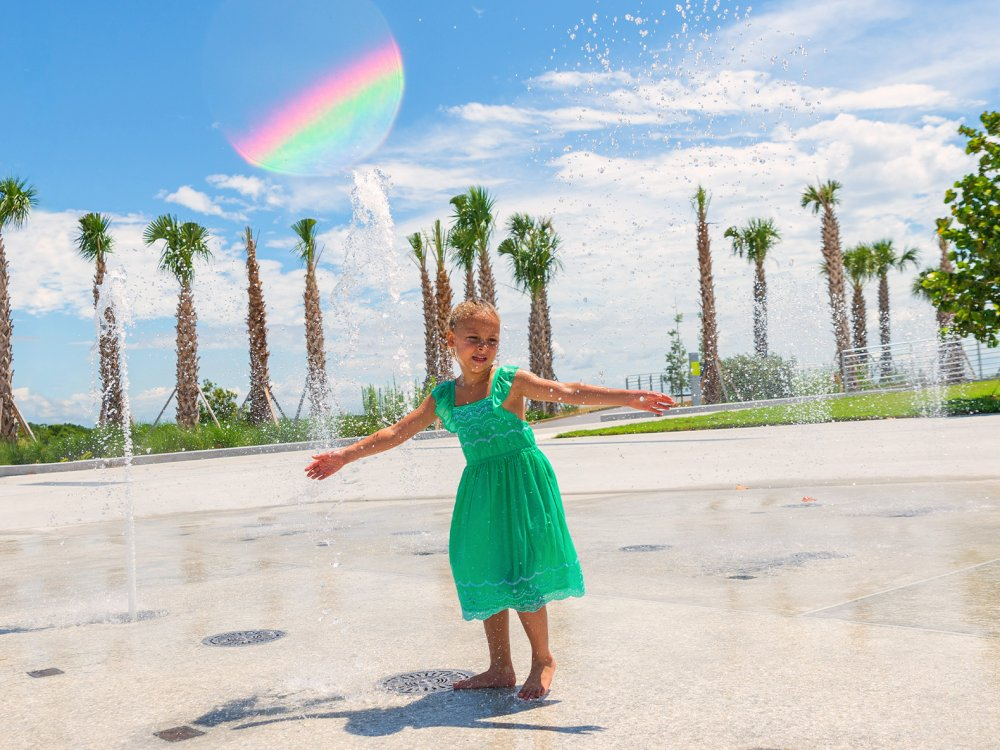 A girl in a green dress playing with the splashing waters at the St. Pete Pier