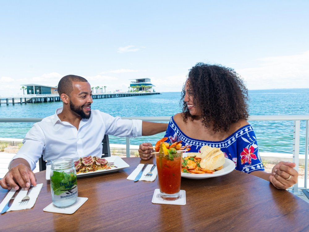 A couple dines and enjoys cocktails at Doc Ford's Rum Bar & Grille with the St. Pete Pier in the background