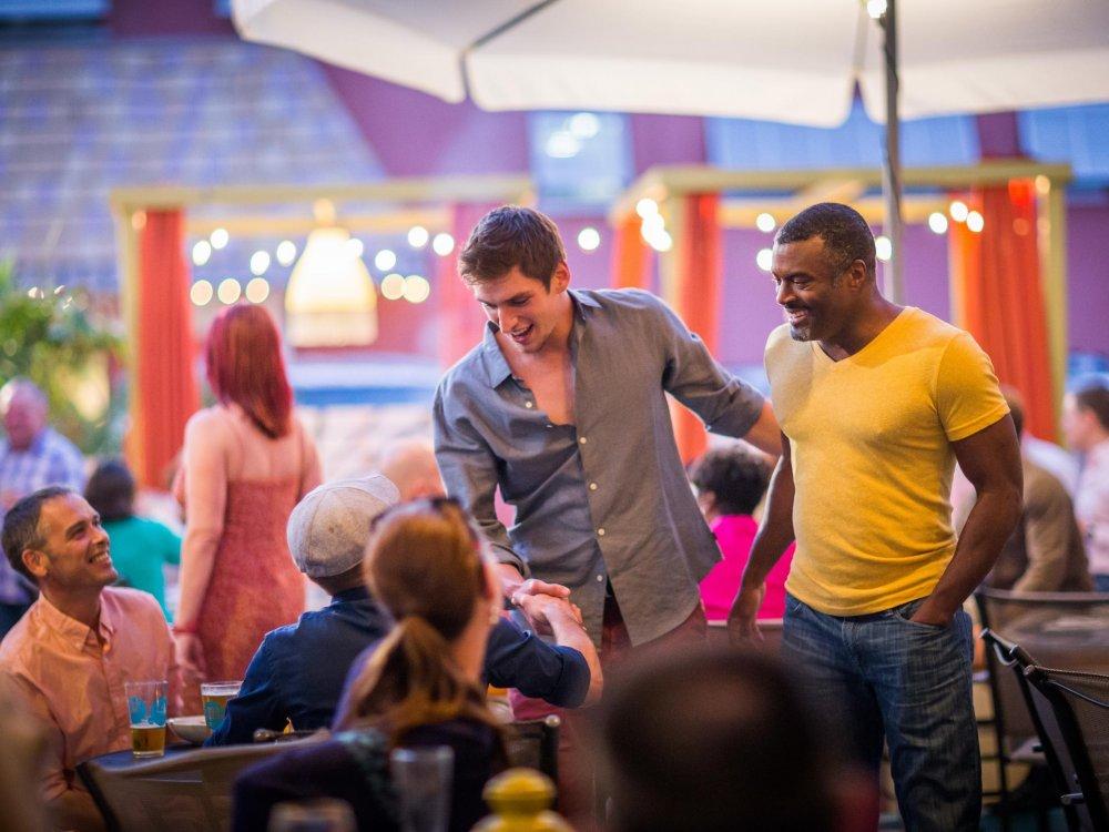 A couple men greet friends at a LGBT+ Bar and Restaurant